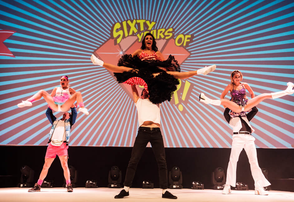Themed dancers on stage opening corporate presentation