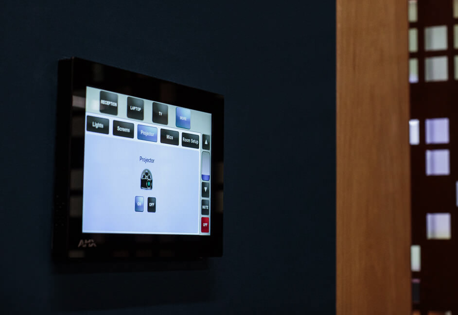 Wired wall mounted touch panel controlling meeting room space with projector, screen, relay screens and source inputs