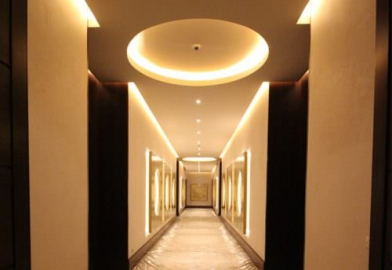 Hallway corridor cove coffer lighting with backlighting to artwork and features in hotel
