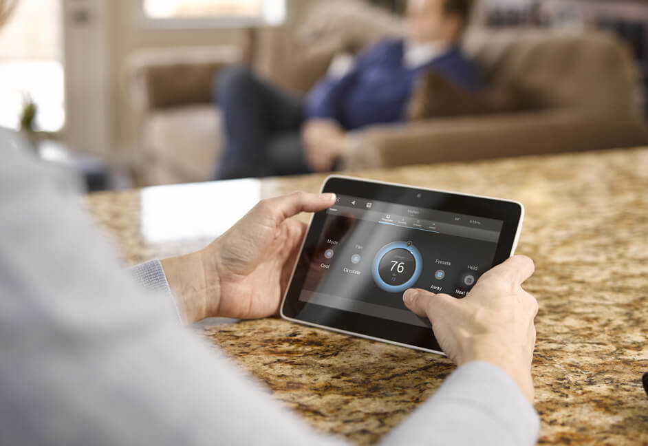 Man using smart home controls on a wireless control 4 touch panel in kitchen for audio streaming, video streaming, blinds control, heating, lighting, comfort, CCTV and security
