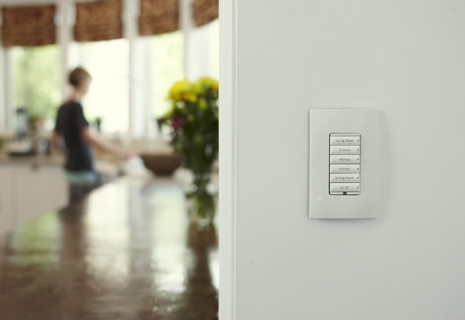 Control 4 keypad wall mounted in home kitchen and living room for home automation controlling lighting, audio sound systems and blinds control