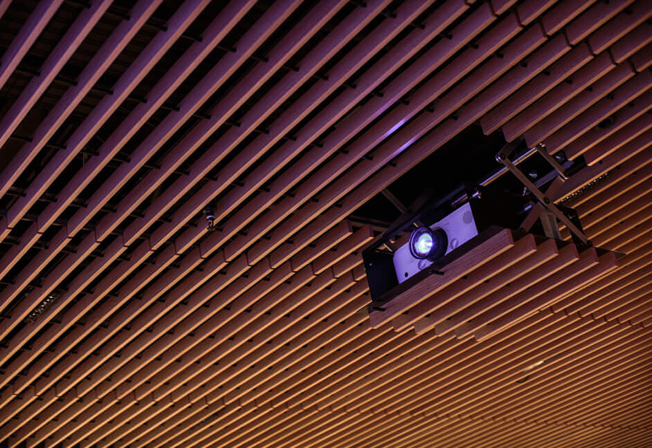 Custom projector lift installed into bespoke slatted ceiling into a townhall meeting space in a large financial company in London
