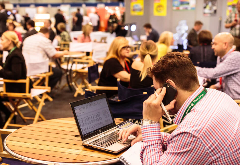 Delegate making phone calls sat a table with laptop at exhibition