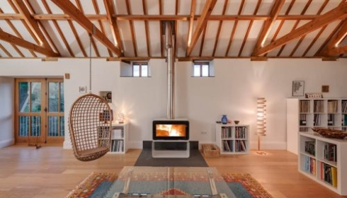 Barn Conversion Cornwall - Sitting room with log burner and lighting in eaves