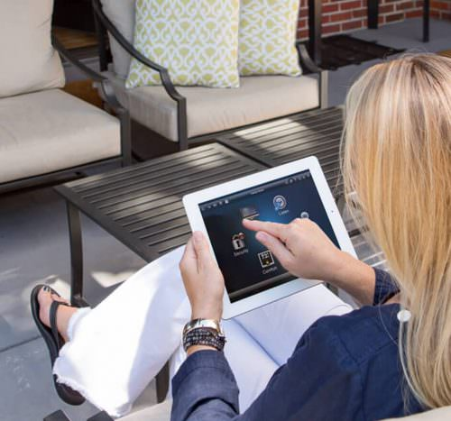 lady sitting outside using control 4 wireless touch panel for home automation and control systems