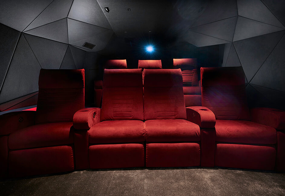 The cavern bespoke cinema design custom geometric cladding and red seats