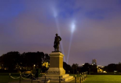 Plymouth Hoe with Theatre Royal search lights in background at night