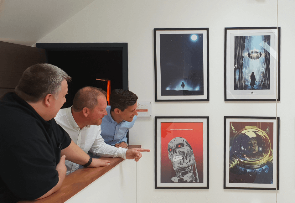 Men pointing to pictures outside home cinema