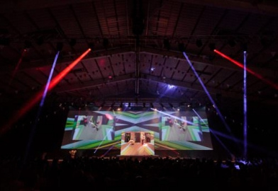 Large projection screen with camera PIPs and stage set for opening performance sequence of Tradeshow at Westpoint Arena Exeter