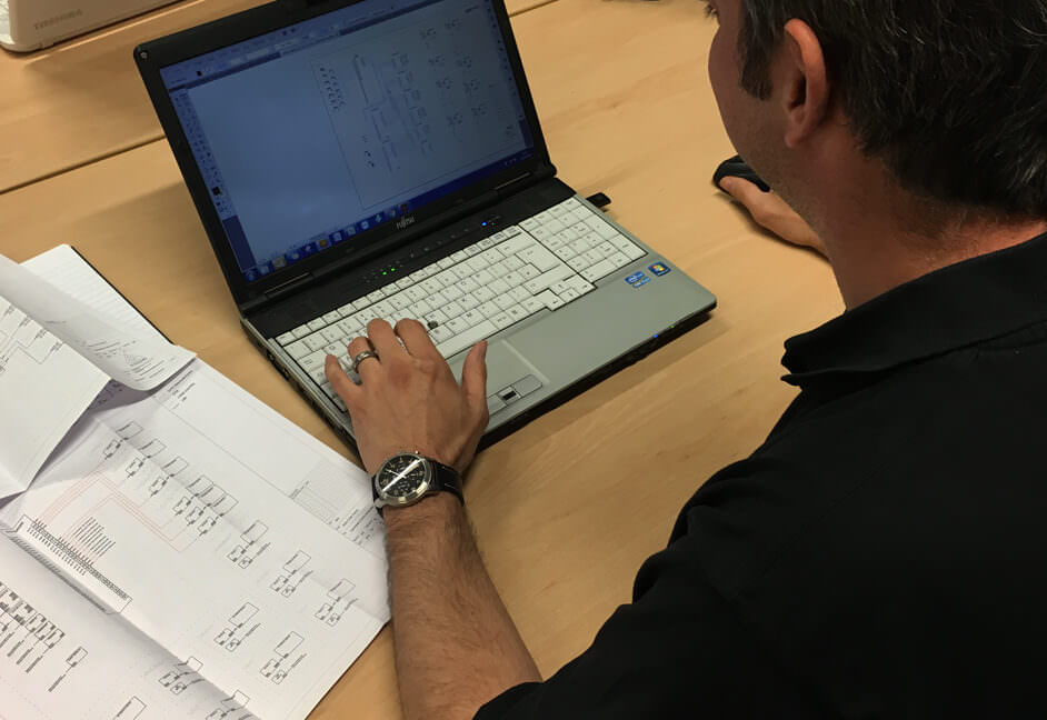 Senior AV Engineer working in an office on his laptop producing audio visual control network schematics and plans